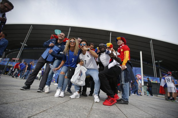 epa05355280 French and Romanian fans cheer for their teams outside the stadium before the UEFA EURO 2016 group A preliminary round match between France and Romania at Stade de France in Saint-Denis, France, 10 June 2016. (RESTRICTIONS APPLY: For editorial news reporting purposes only. Not used for commercial or marketing purposes without prior written approval of UEFA. Images must appear as still images and must not emulate match action video footage. Photographs published in online publications (whether via the Internet or otherwise) shall have an interval of at least 20 seconds between the posting.) EPA/YOAN VALAT EDITORIAL USE ONLY