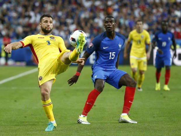 epa05355774 Razvan Rat of Romania (L) in action against Paul Pogba (C) of France during the UEFA EURO 2016 group A preliminary round match between France and Romania at Stade de France in Saint-Denis, France, 10 June 2016. (RESTRICTIONS APPLY: For editorial news reporting purposes only. Not used for commercial or marketing purposes without prior written approval of UEFA. Images must appear as still images and must not emulate match action video footage. Photographs published in online publications (whether via the Internet or otherwise) shall have an interval of at least 20 seconds between the posting.) EPA/YOAN VALAT EDITORIAL USE ONLY