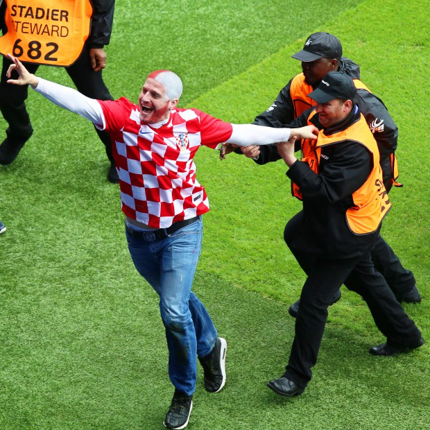 epa05359139 A Croatian pitch invader (L) celebrates his team's 1-0 lead during the UEFA EURO 2016 group D preliminary round match between Turkey and Croatia at Parc des Princes in Paris, France, 12 June 2016. (RESTRICTIONS APPLY: For editorial news reporting purposes only. Not used for commercial or marketing purposes without prior written approval of UEFA. Images must appear as still images and must not emulate match action video footage. Photographs published in online publications (whether via the Internet or otherwise) shall have an interval of at least 20 seconds between the posting.) EPA/SRDJAN SUKI EDITORIAL USE ONLY