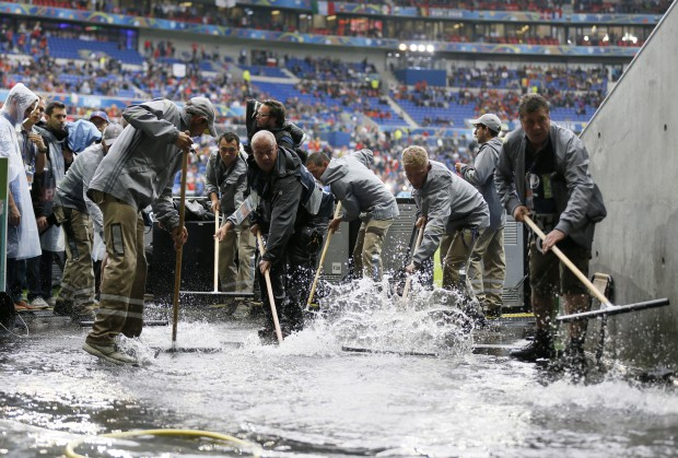 epa05362518 Workers clear water away prior to the UEFA EURO 2016 group E preliminary round match between Belgium and Italy at Stade de Lyon in Lyon, France, 13 June 2016. (RESTRICTIONS APPLY: For editorial news reporting purposes only. Not used for commercial or marketing purposes without prior written approval of UEFA. Images must appear as still images and must not emulate match action video footage. Photographs published in online publications (whether via the Internet or otherwise) shall have an interval of at least 20 seconds between the posting.) EPA/SERGEY DOLZHENKO EDITORIAL USE ONLY