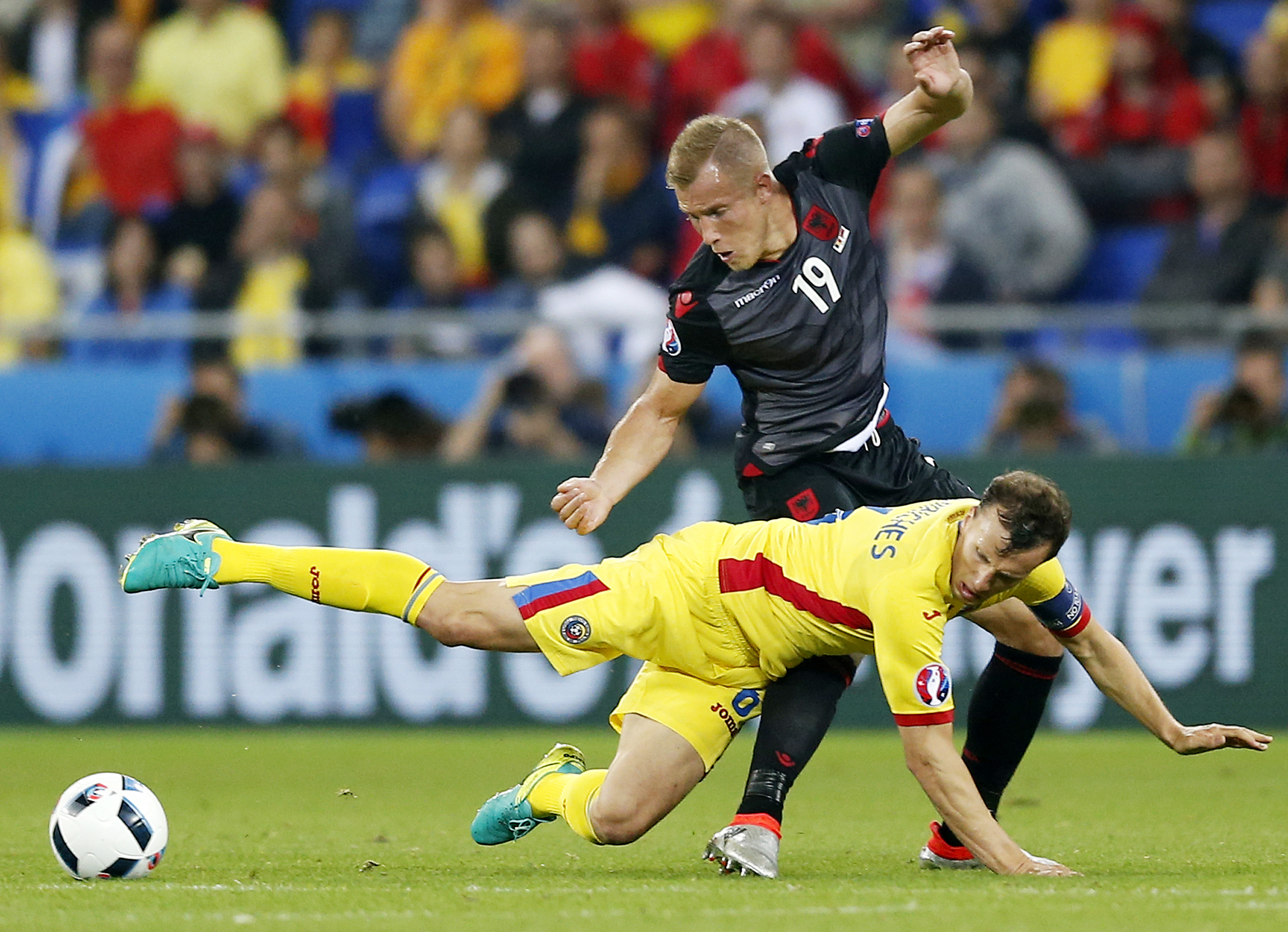 epa05378429 Vlad Chiriches of Romania in action against Bekim Balaj (standing) of Albania during the UEFA EURO 2016 group A preliminary round match between Romania and Albania at Stade de Lyon in Lyon, France, 19 June 2016. (RESTRICTIONS APPLY: For editorial news reporting purposes only. Not used for commercial or marketing purposes without prior written approval of UEFA. Images must appear as still images and must not emulate match action video footage. Photographs published in online publications (whether via the Internet or otherwise) shall have an interval of at least 20 seconds between the posting.) EPA/YURI KOCHETKOV EDITORIAL USE ONLY