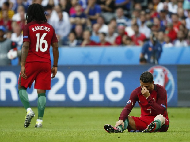 epa05419183 Cristiano Ronaldo (R) of Portugal reacts after picking up an injury during the UEFA EURO 2016 Final match between Portugal and France at Stade de France in Saint-Denis, France, 10 July 2016. (RESTRICTIONS APPLY: For editorial news reporting purposes only. Not used for commercial or marketing purposes without prior written approval of UEFA. Images must appear as still images and must not emulate match action video footage. Photographs published in online publications (whether via the Internet or otherwise) shall have an interval of at least 20 seconds between the posting.) EPA/IAN LANGSDON EDITORIAL USE ONLY
