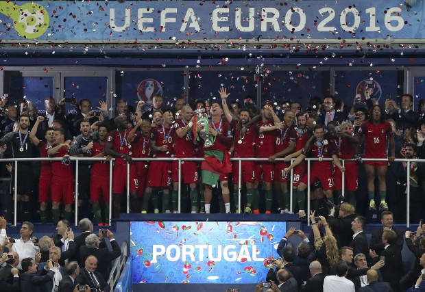 epa05419784 Portuguese captain Cristiano Ronaldo (C) lifts the trophy flanked by teammates after winning the UEFA EURO 2016 Final match between Portugal and France at Stade de France in Saint-Denis, France, 10 July 2016. (RESTRICTIONS APPLY: For editorial news reporting purposes only. Not used for commercial or marketing purposes without prior written approval of UEFA. Images must appear as still images and must not emulate match action video footage. Photographs published in online publications (whether via the Internet or otherwise) shall have an interval of at least 20 seconds between the posting.) EPA/MIGUEL A. LOPES EDITORIAL USE ONLY