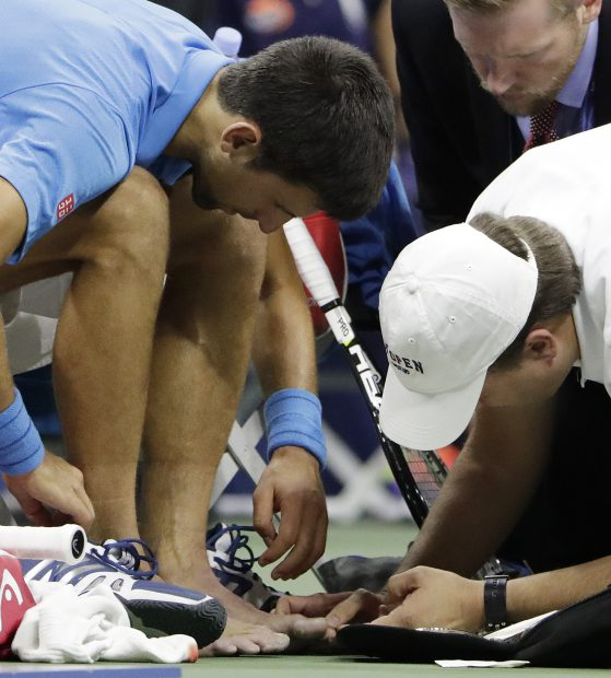 epa05535698 Novak Djokovic of Serbia has toes on both feet bandaged during a medical timeout as he plays Stan Wawrinka of Switzerland during the men's final on the final day of the US Open Tennis Championships at the USTA National Tennis Center in Flushing Meadows, New York, USA, 11 September 2016. The US Open runs through September 11. EPA/VINCENT LAFORET