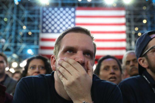 Un susținător al lui Hillary Clinton îl ascultă pe purtătorul de cuvânt al campaniei democrate