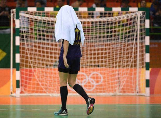 Imagine cu putere de simbol: Gabriela Perianu, ascunzâdu-se de rușine sub prosop, după eliminarea prematură a naționalei feminine de handbal a României de la Jocurile Olimpice. (FOTO: EPA)