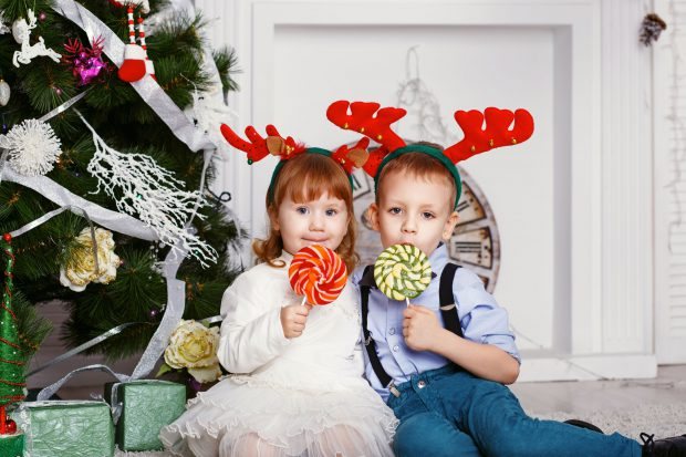 49810332 - little girl and boy in reindeer antlers eating a lollipops. portrait of two funny little kids with a delicious candies in the hands. christmas and new year concept. happy children and family in anticipation of the new year and christmas.