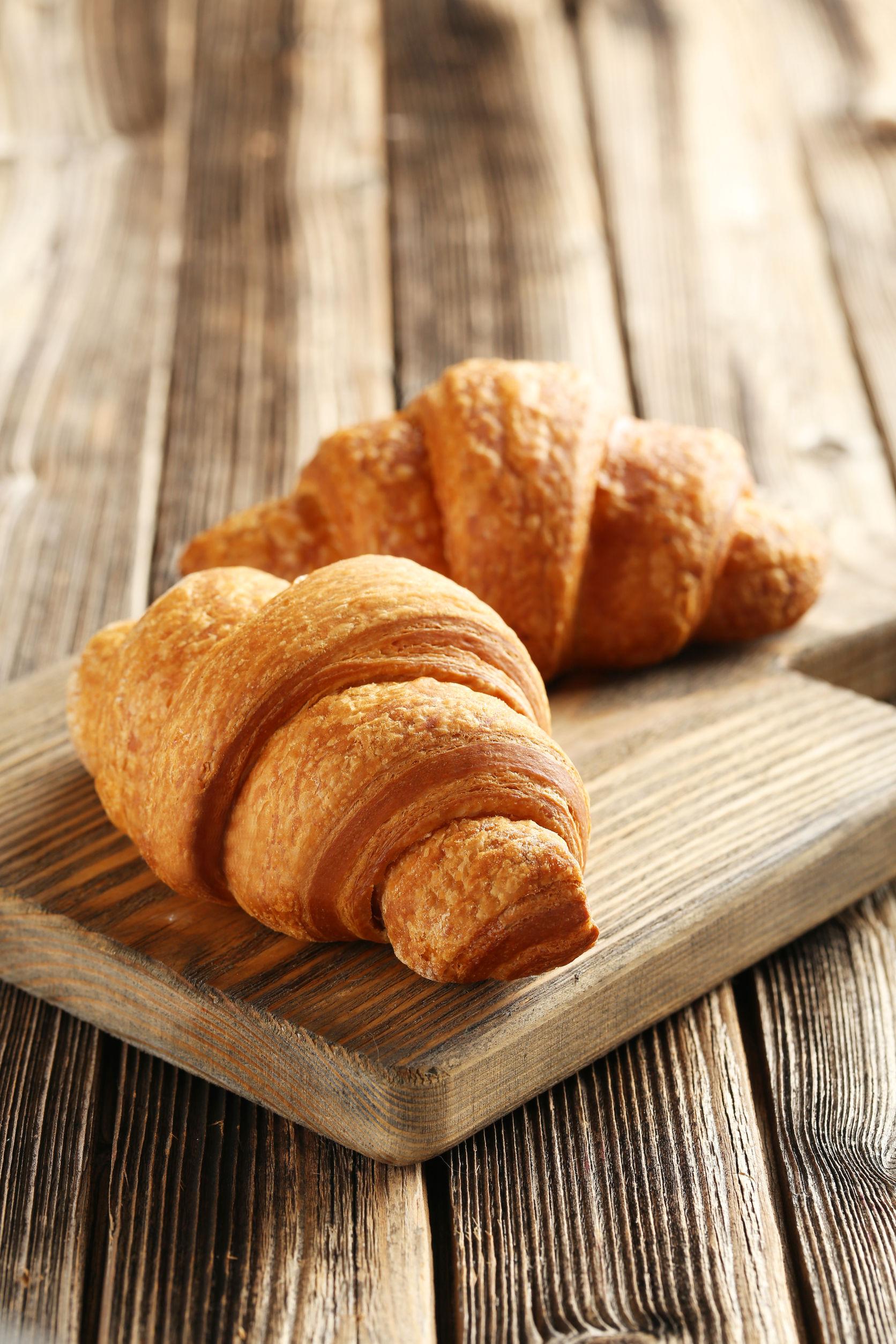 48936250 - tasty croissants on brown wooden background