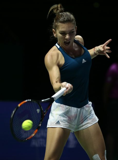 epa05605186 Simona Halep of Romania in action against Dominika Cibulkova of Slovakia during their singles round robin match of the BNP Paribas WTA Finals 2016 held at the Indoor Stadium in Singapore, 27 October 2016. EPA/WALLACE WOON