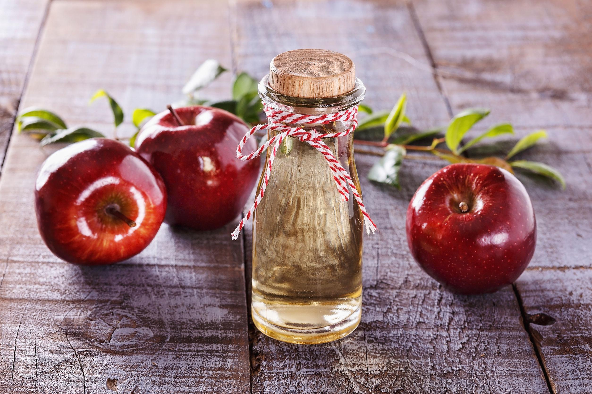 43642807 - apple cider vinegar and red apples over rustic wooden background
