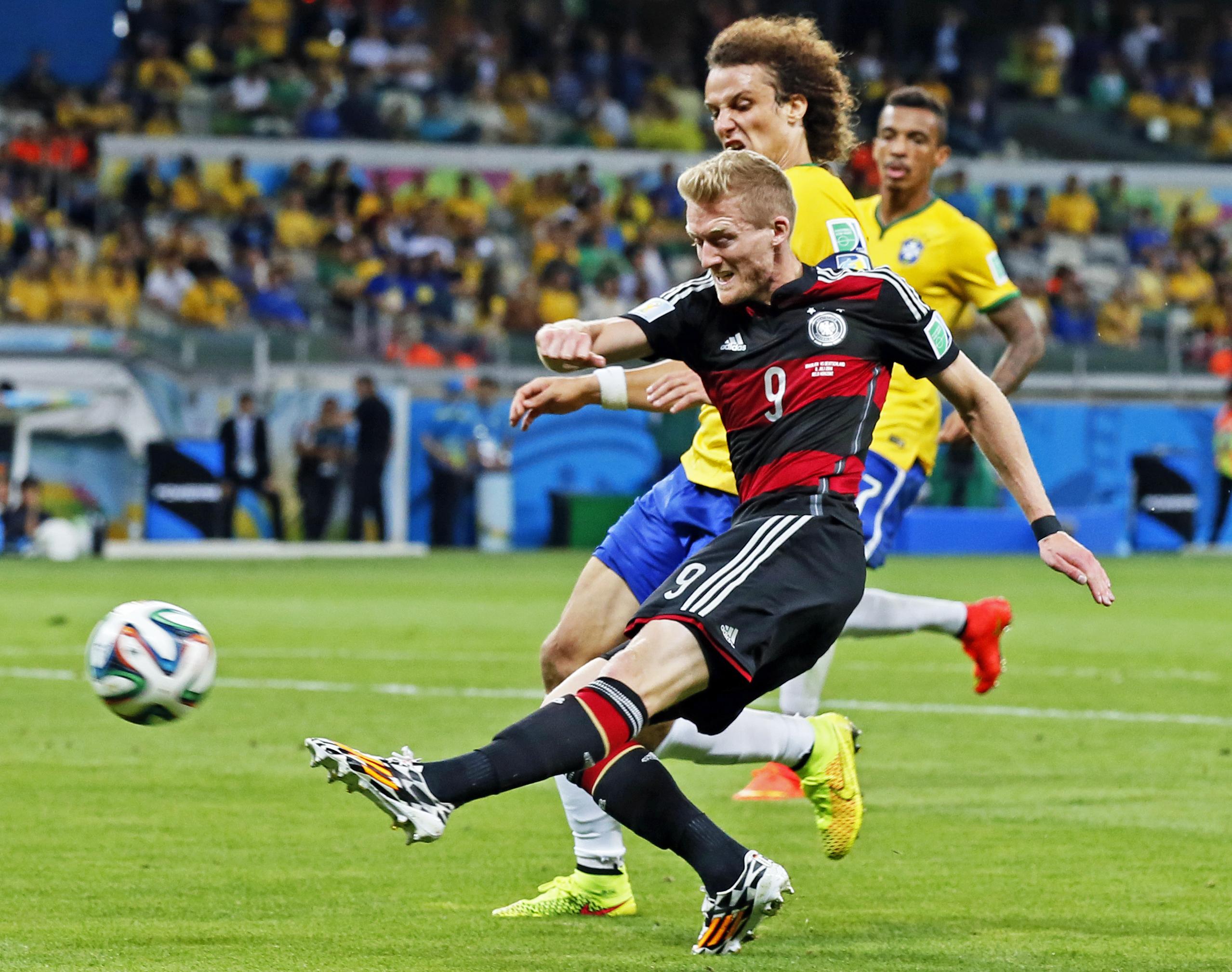 Neamțul André Schürrle (prim-plan) șutează de lângă David Luiz și înscrie al șaptelea gol al Germaniei în semifinala de poveste cu Brazilia, câștigată cu 7-1 la Cupa Mondială din 2014. (FOTO: EPA)