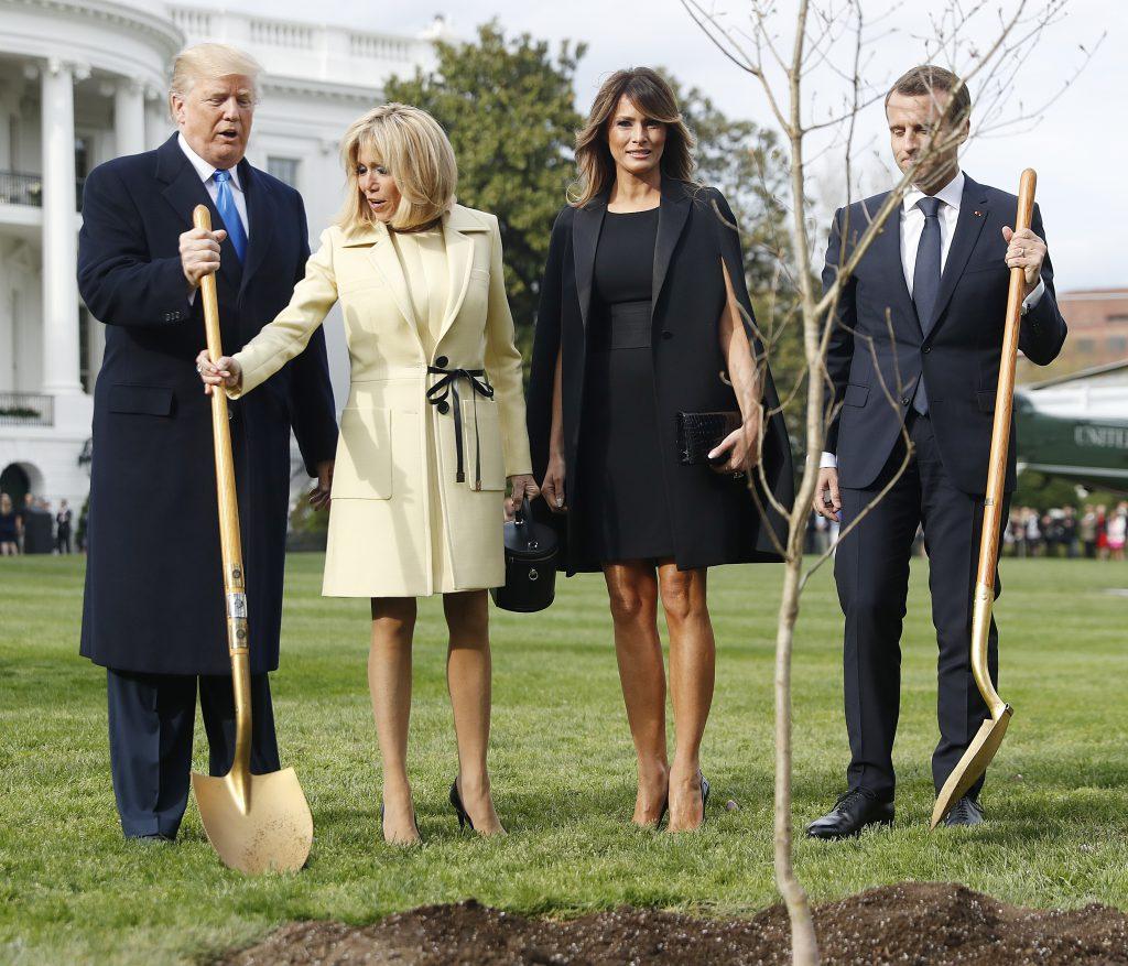 Ce ținute au ales Brigitte Macron și Melania Trump. brigitte Macron în galben și Melania trump în negru alături de soții lor la plantarea stejarului