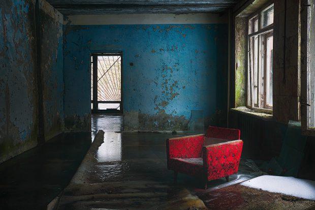 Biroul unui director, cu un fotoliu roşu aşezat în dreptul ferestrelor sparte, şi un covor multicolor aflat pe pe jumătate sub apa îngheţată de pe podea