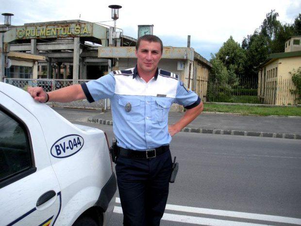Celebrul polițist brașovean Marian Godină, sprijinit de masina de poliție, în dreptul Uzinei Rulmentul S.A.
