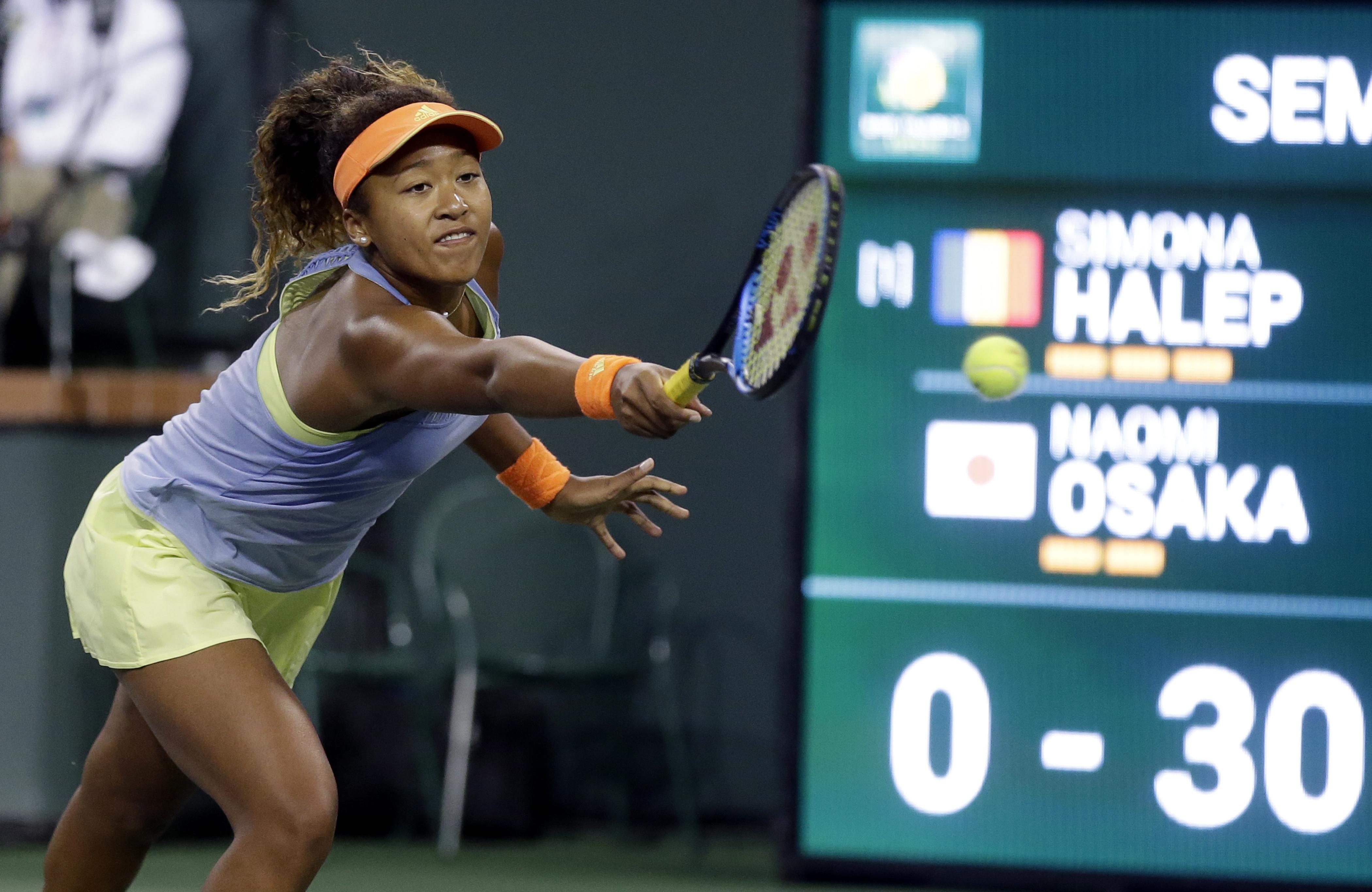 Naomi Osaka, întinzându-se după minge în timpul unei partide cu Simona Halep. (FOTO: EPA)