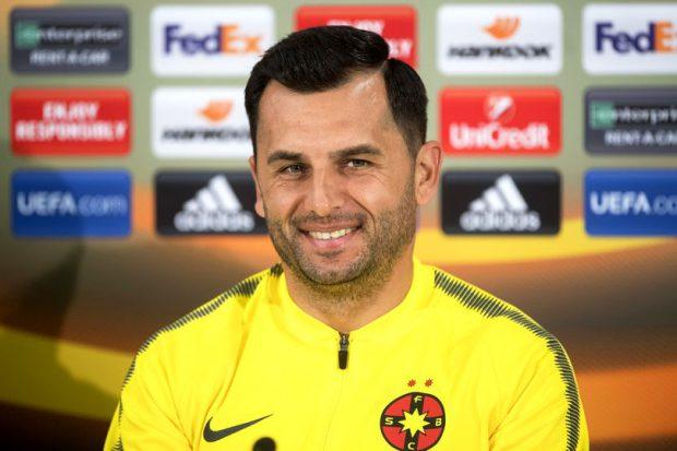 Nicolae Dică. Antrenorul FCSB, Nicolae Dică, într-o bluză glbenă, cu sigla echipei... zâmbește, în timpul unei conferințe de presă