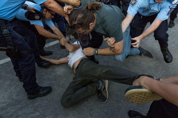 Un protestatar e culcat la pâmânt, iar un altul este bruscat de jandarmi, în Piața Victoriei din Capitală