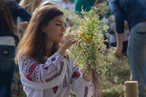 Sărbătoarea de Sânziene - Drăgaica. Femeie care își impleteste coroana din flori pentru Sânziene
