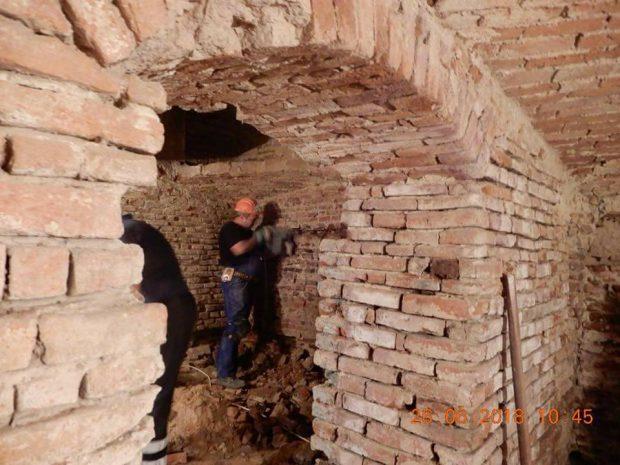 Fotografie postată pe pagina de Facebook a Primăriei Capitalei, în care un muncitor găureşte un zid din subsolul unei clădiri istorice