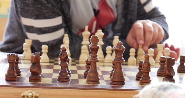 De ce trebuie părinții să anunțe autoritățile când pleacă peste hotare. Copil jucând șah