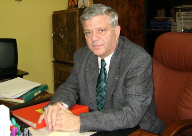 Ioan Lascu, stând la un birou, cu mâinile încrucișate