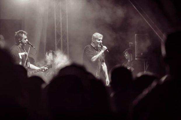 Trupa Holograf donează banii primiți pentru spectacolul din Sectorul 5. Fotografie alb-negru din timpul unui concert al trupei Holograf, cu Dan Bittman la microfon