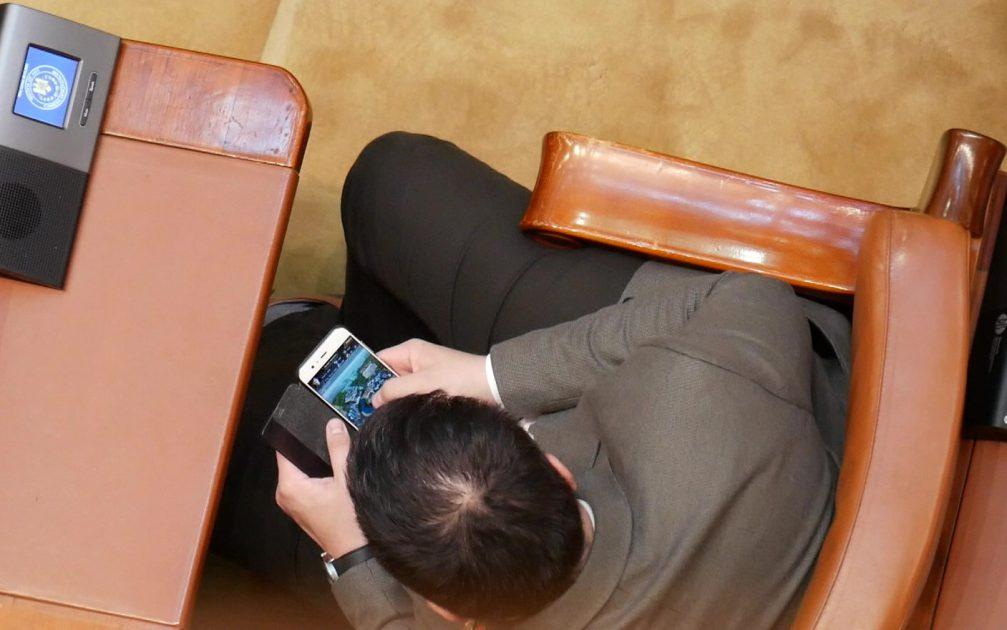 Un parlamentar se joacă pe telefon în timpul Şedinţei solemne de Centenar