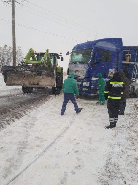 Camion blocat în zăpada. Lângă el se află angajați de la Drumuri și un pompier, alături de un excavator