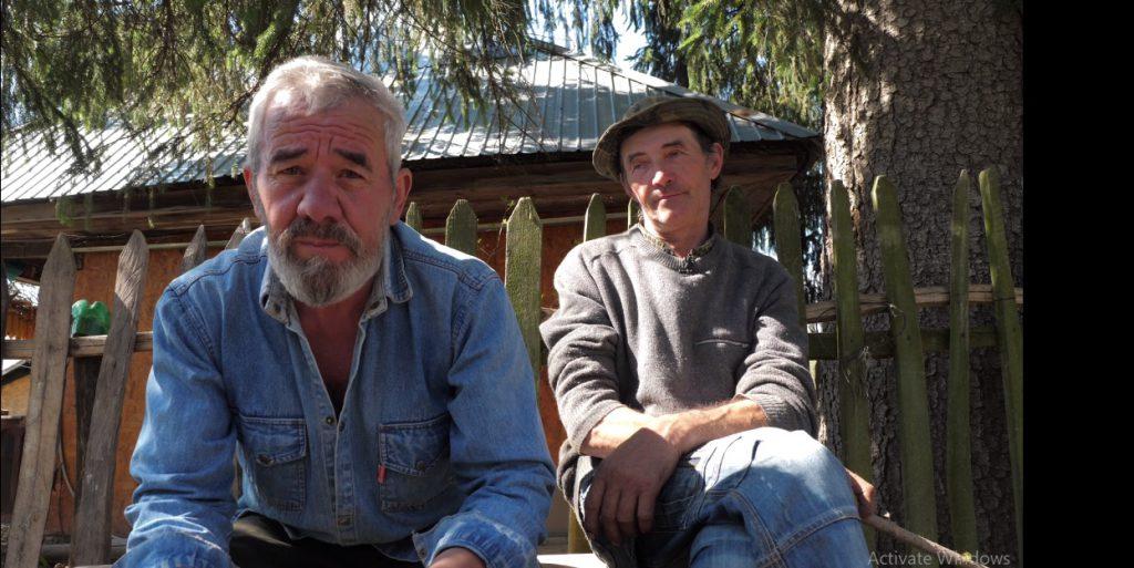 Ion Toader, fratele lui Gheorghe Toader, şi vecinul lui, Doru Pătru, stau de vorbă pe singura bancă din sat.