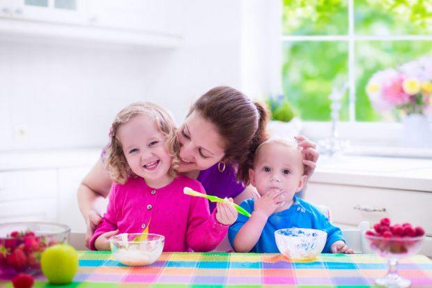 Mic dejun pentru copii - mama cu doi copii care servesc micul dejun
