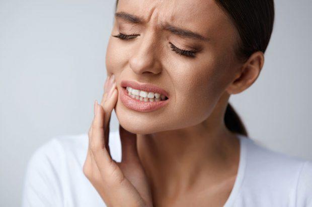 Durere de dinți - femeie care are o durere de dinți