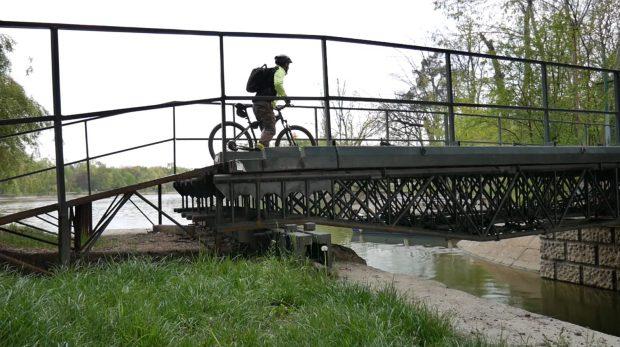 Un biciclist traversează podul pietonal din Parcul Herăstrău