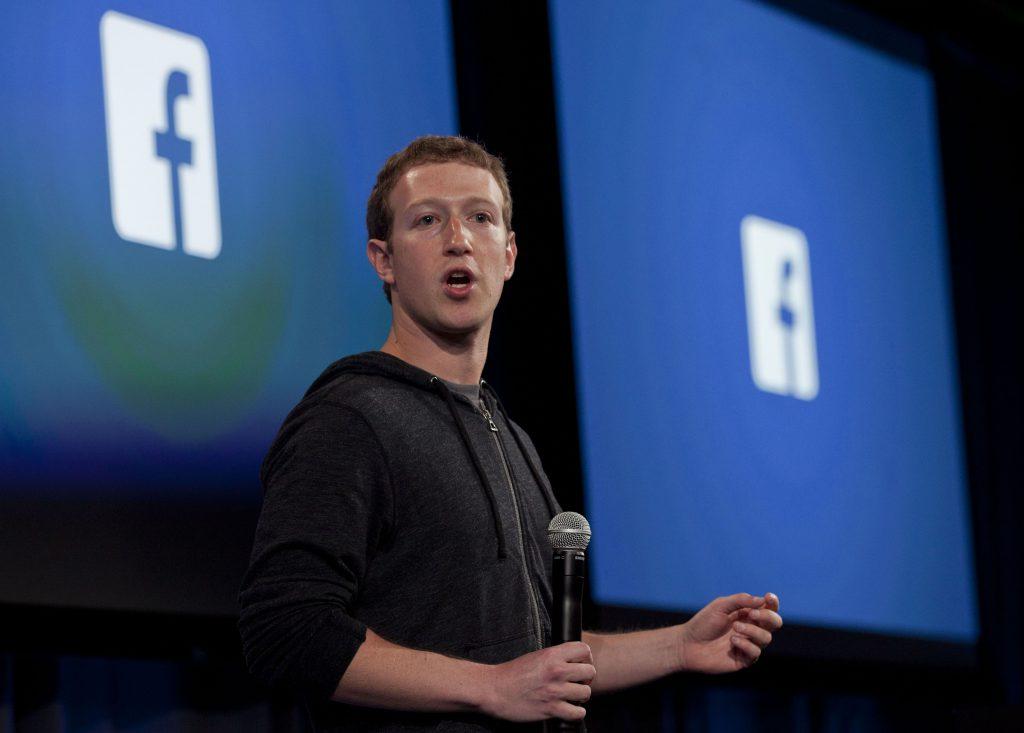 SUA cer Facebook să nu lanseze criptomoneda Libra până nu sunt rezolvate problemele legate de spălarea de bani. Mark Zuckerberg cu logo-uri Facebook în spate