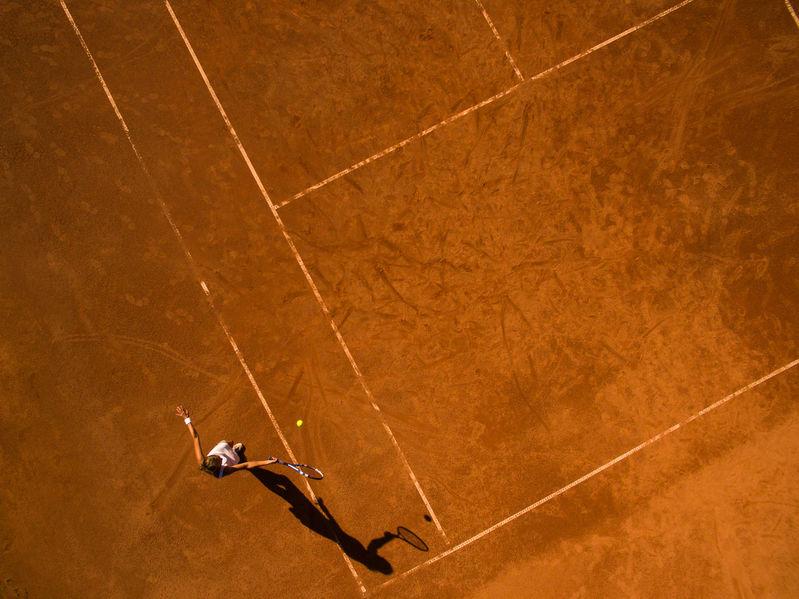 Tipuri de teren de tenis - teren pe zgură. Femeie jucând tenis pe teren de zgură