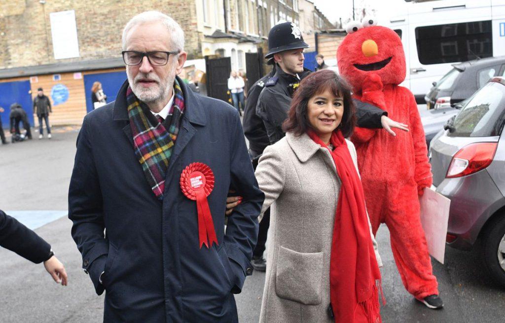 Jeremy Corbyn, alături de soția sa și de un protestatar îmbrăcat în costumul personajului Elmo, din Sesame Street, la secția de votare FOTO: EPA