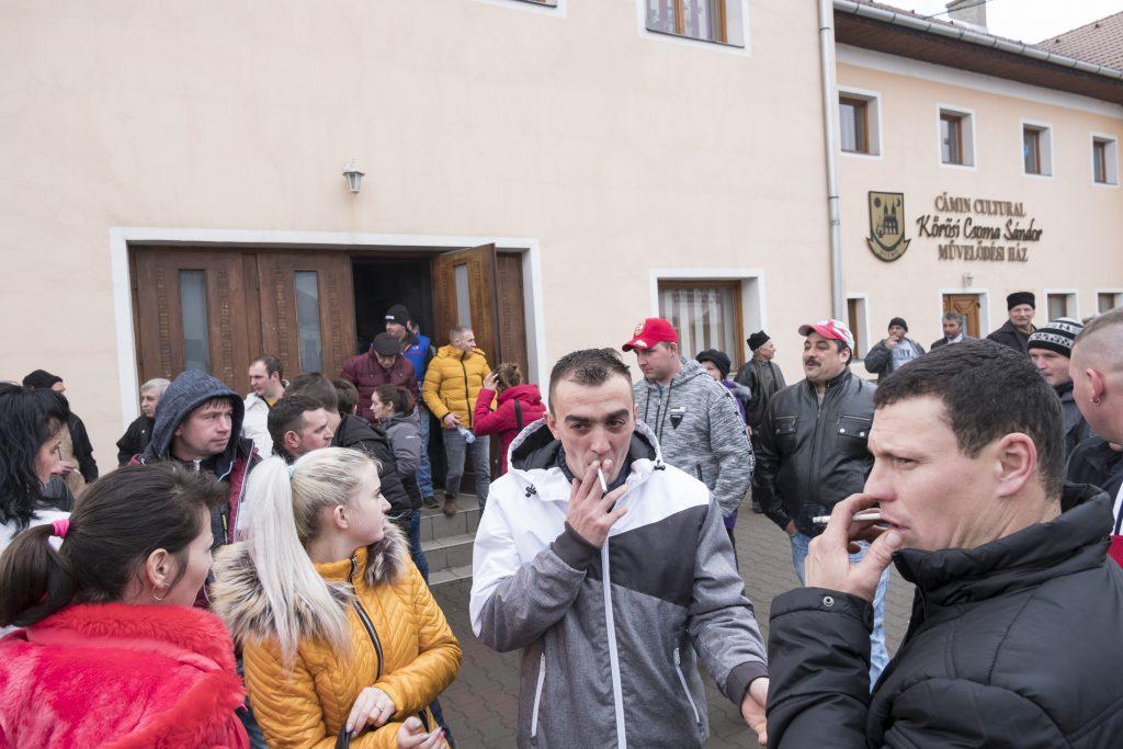 Zeci de locuitori ai comunei Ditrău vorbesc în fața căminului cultural după terminarea adunării sătești
