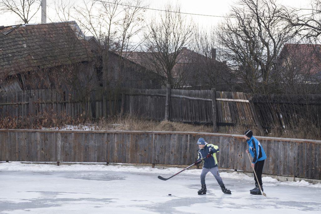 Doi copii joacă hockey pe un patinoar artificial în spatele căminului cultural din Ditrău.